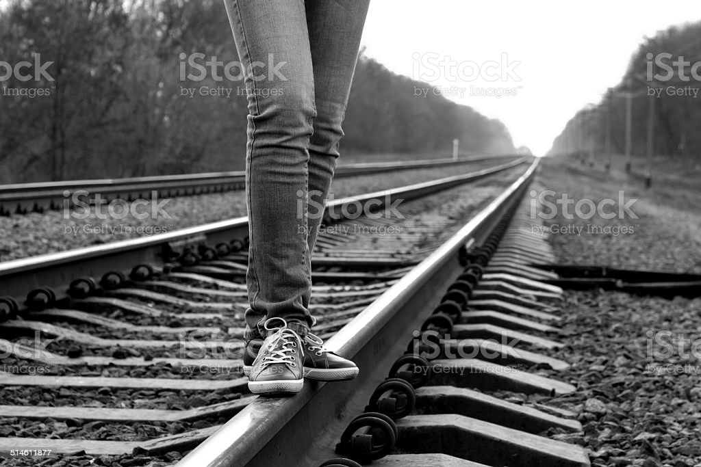 Girl walking across railroad. B&W image stock photo