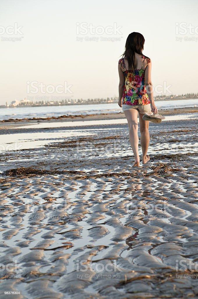 Ragazza cammina lungo la spiaggia foto stock royalty-free