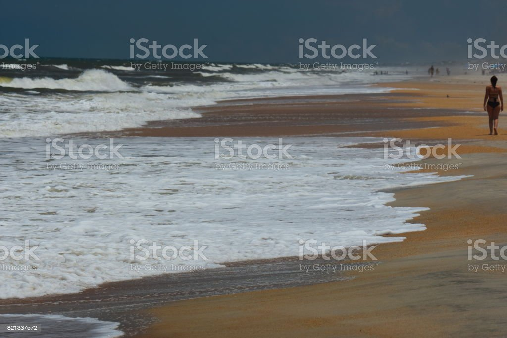 Girl Walking Along Surf Line On Florida Beach With People In