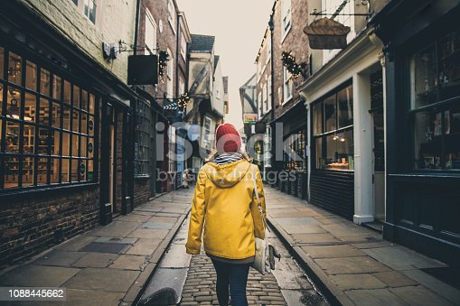 A rear view of a female in a bright yellow coat walking along the historic street known as The Shambles in York, UK which is a popular tourist destination in this Yorkshire city.