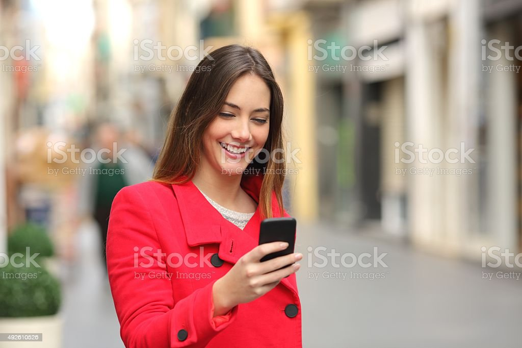 Girl walking and texting on smartphone in the street stock photo