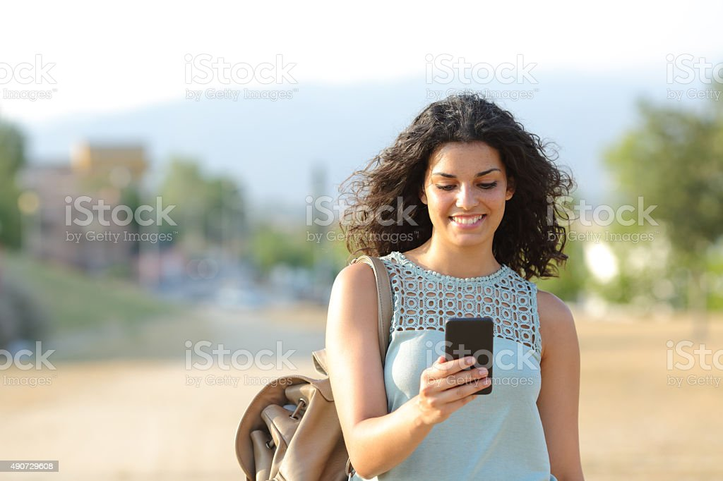 Girl walking and using a smart phone in a town royalty-free stock photo