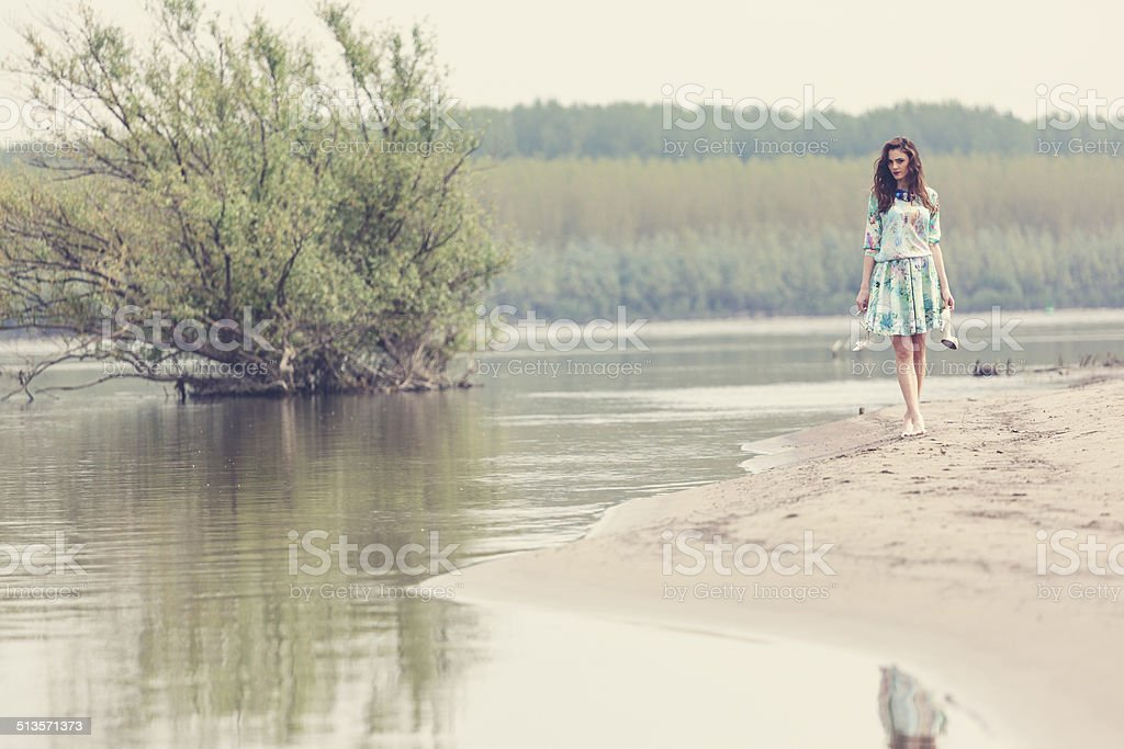 Girl walking at lake shore stock photo