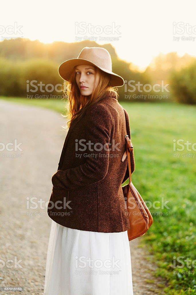 girl walking down in sunset light stock photo