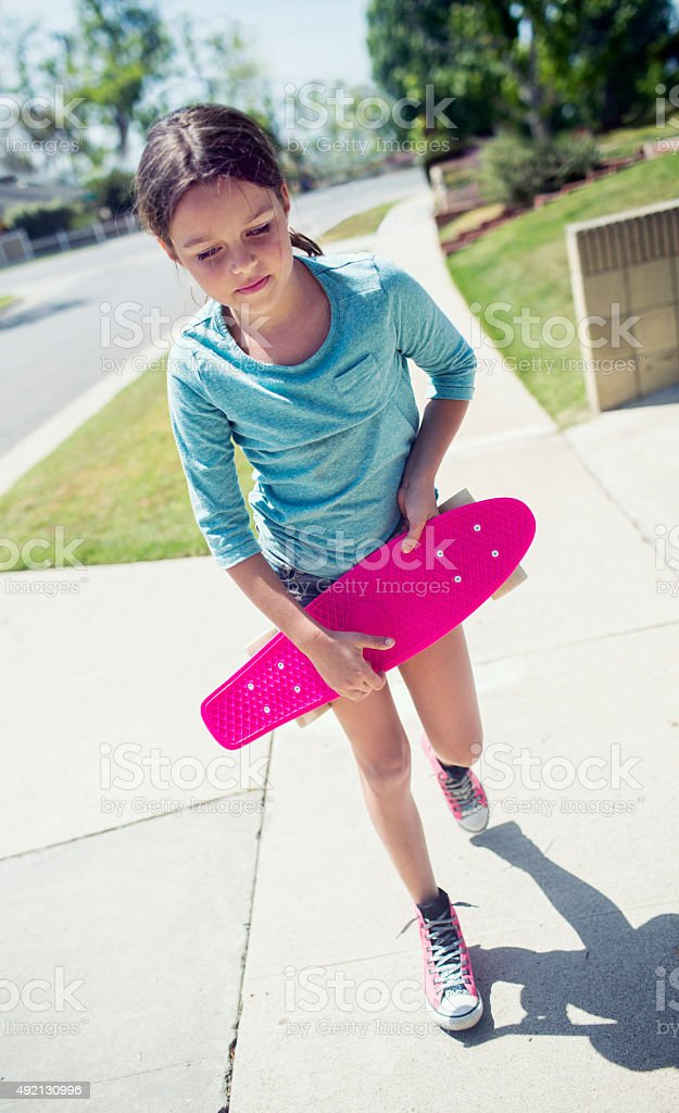 Girl walking down the sidewalk with skateboard stock photo
