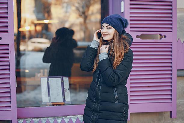 girl walking in a winter city - ダウンジャケット ストックフォトと画像