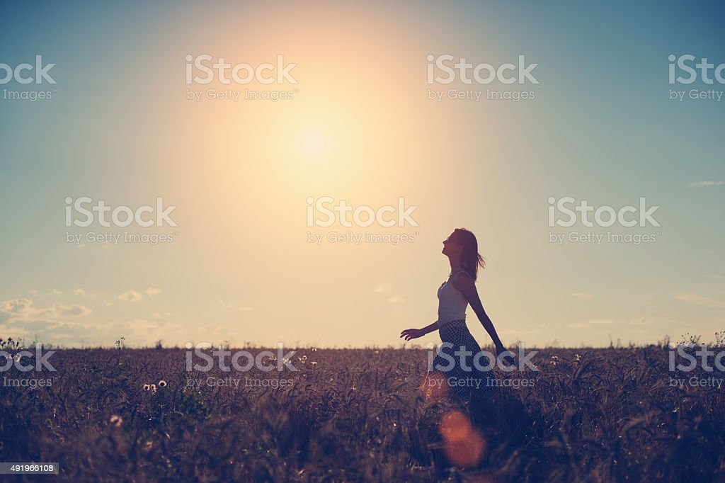 Girl walking in the field in the evening stock photo