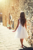 Teenage girl or a young woman walking sunny narrow street of a charming italian town. The girl is wearing a white dress.