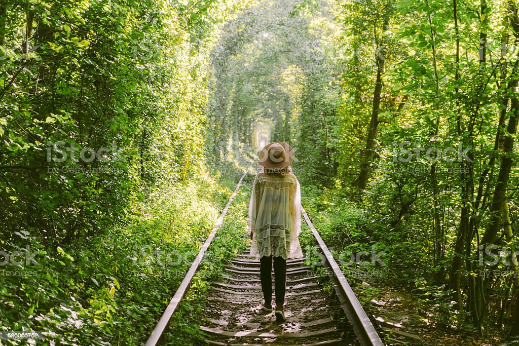 Girl walking in tree tunnel - Royalty-free Adult Stock Photo