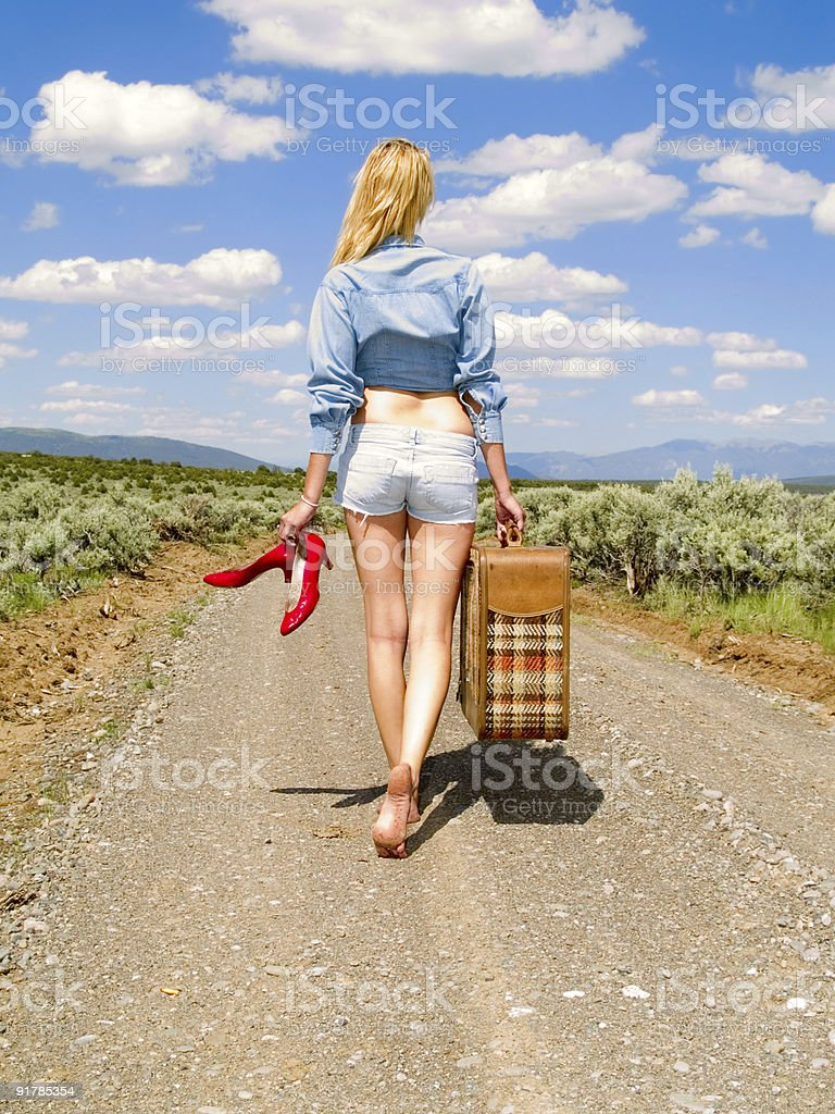 Girl walking on a dirt road with suitcase stock photo