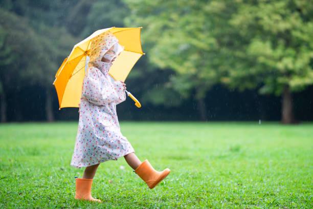 mädchen zu fuß an einem regnerischen tag - regenzeit stock-fotos und bilder