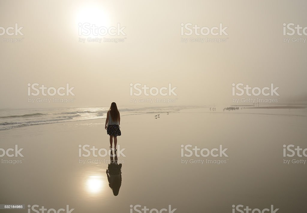 Girl walking on beautiful foggy beach. stock photo