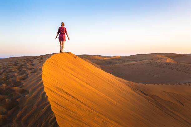 mädchen zu fuß auf sanddünen in trockenen wüsten bei sonnenuntergang und tragen kleid, landschaft der sahara oder des nahen ostens - sahara stock-fotos und bilder