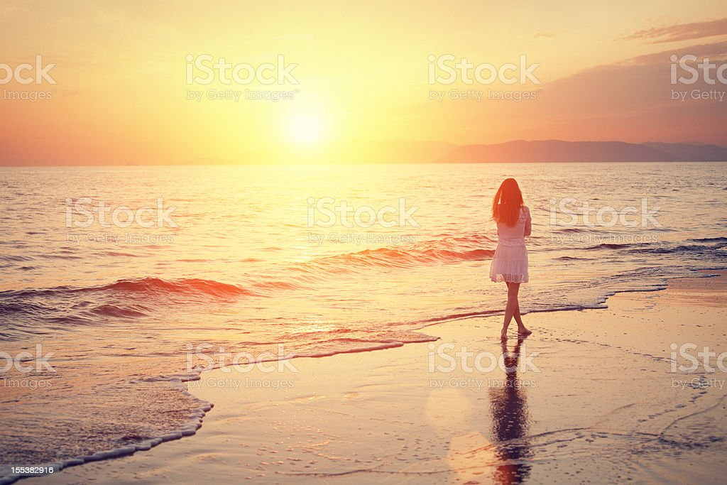 girl walking on the beach at sunset royalty-free stock photo