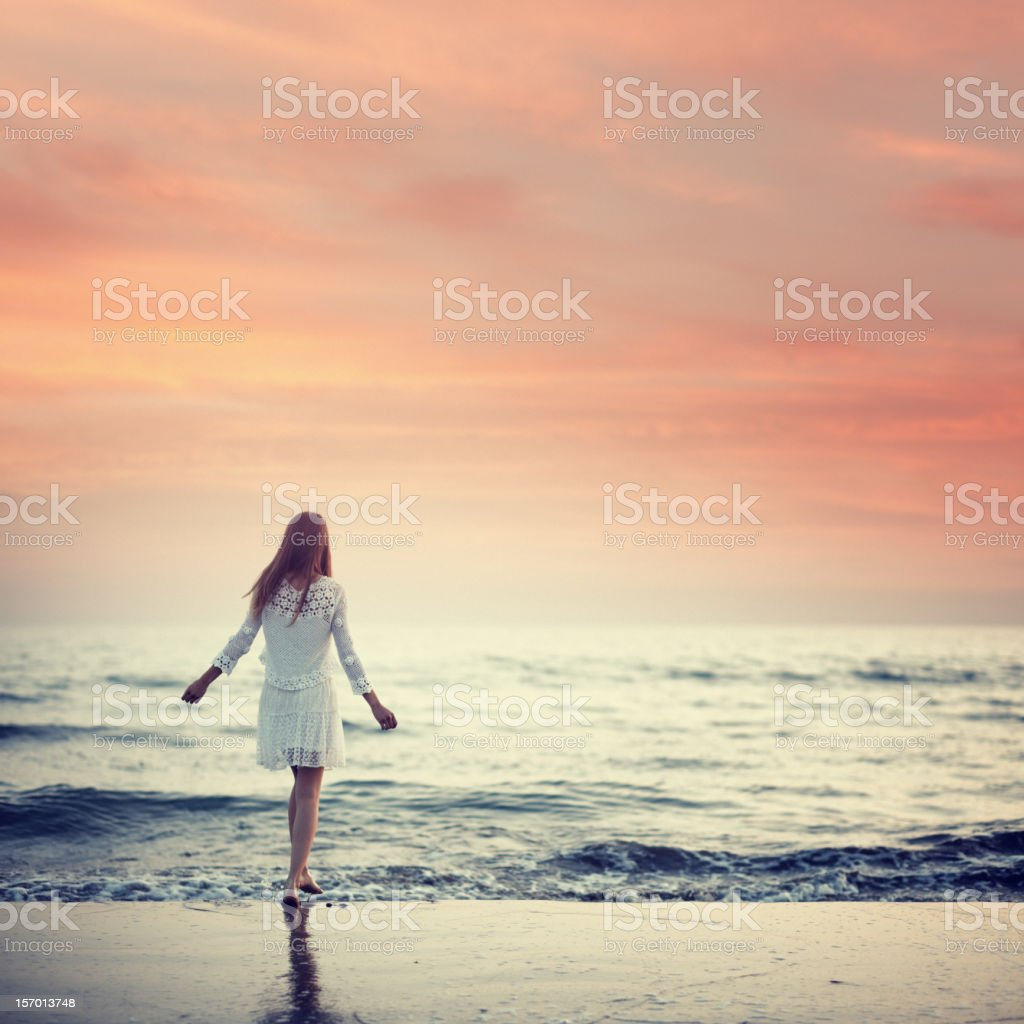 girl walking on the beach at sunset stock photo