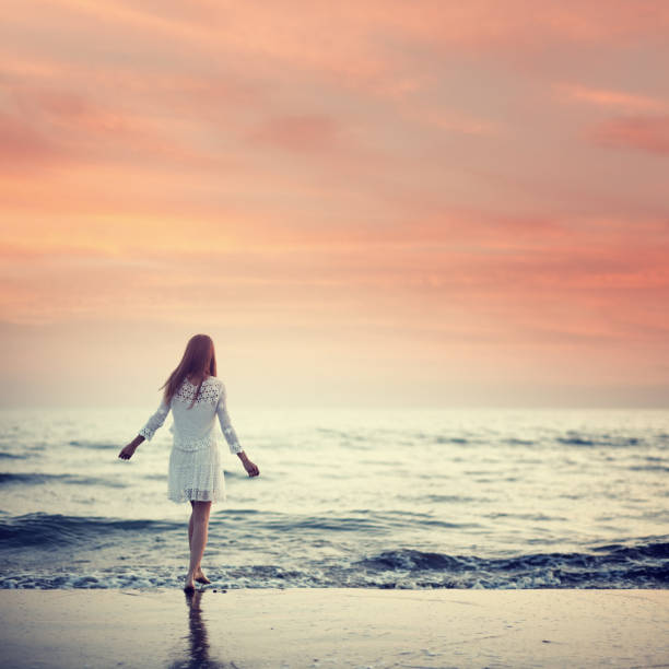 girl walking on the beach at sunset - one young woman only stock pictures, royalty-free photos & images