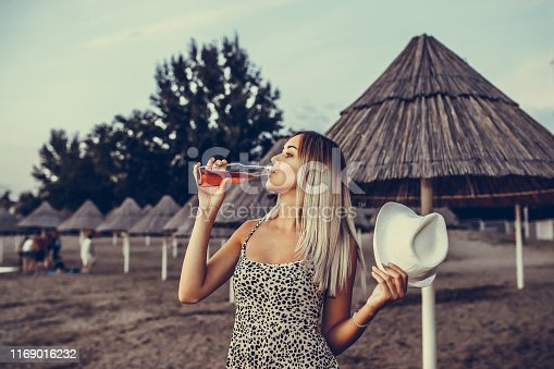 Young smiling woman with a hat in her hand enjoys walking on the sandy beach in the evening while drinking beer of a bottle. She is very happy