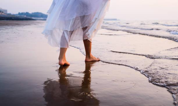Girl walking on the beach stock photo