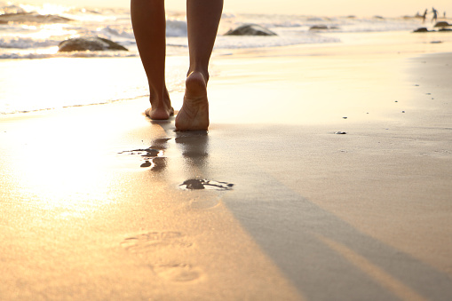 Girl walking on wet sandy beach leaving footprints stock photo