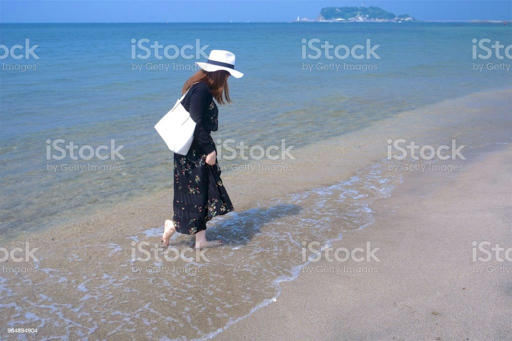 Girl walking on wet sandy beach royalty-free stock photo