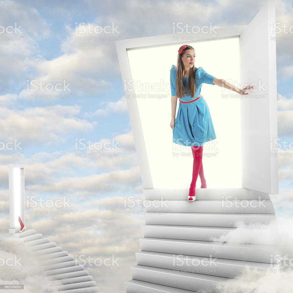 Girl walking through a magic door in sky stock photo