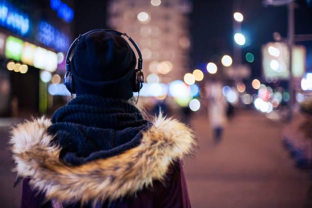flicka vandrar genom natt gata som lyssnar på musik - cold street bildbanksfoton och bilder