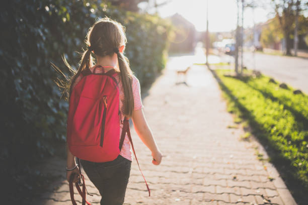 girl walking to school - school building stock photos and pictures