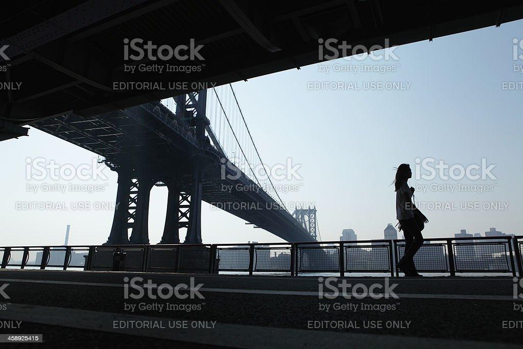 NYC girl walking to work under Manhattan Bridge with iPod stock photo