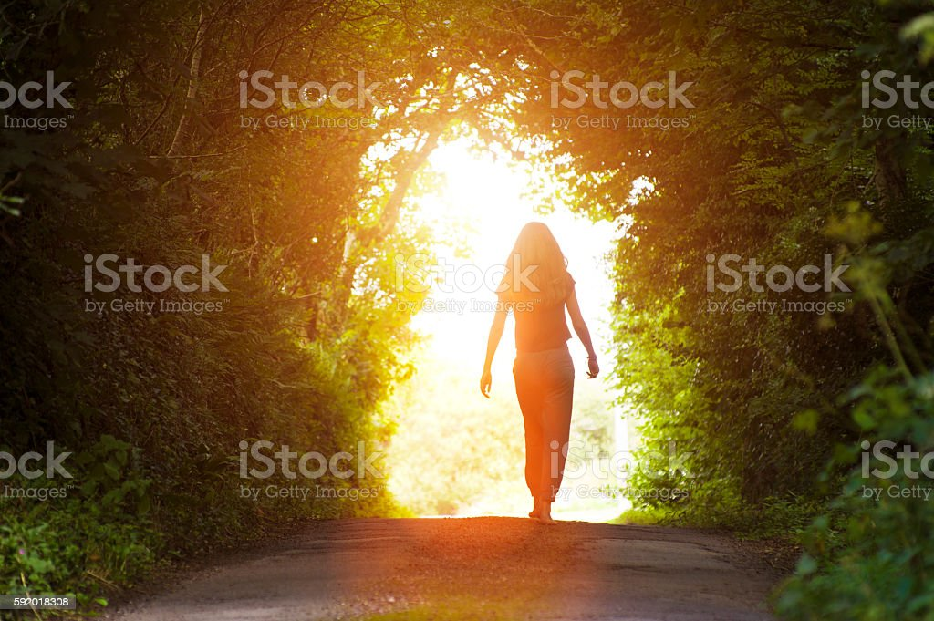 Girl walking towards the light stock photo