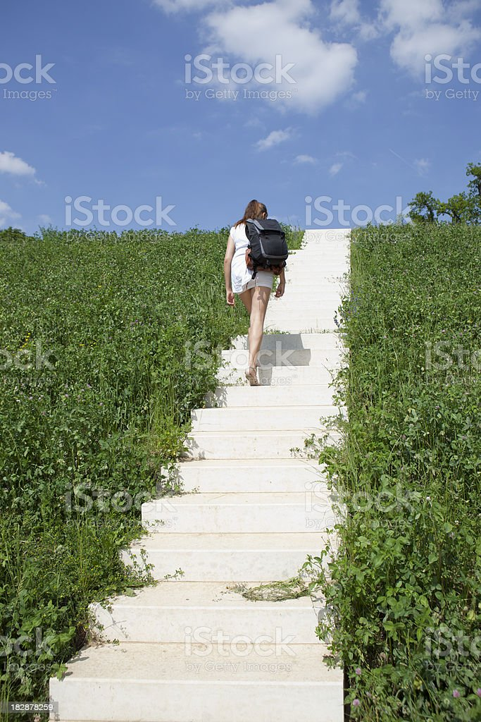 Girl walking up a flight of stairs to nowhere stock photo