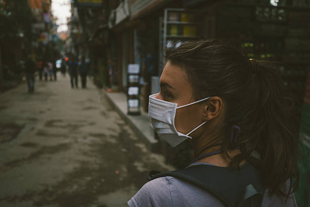 Girl walking wearing a mask in the city street stock photo