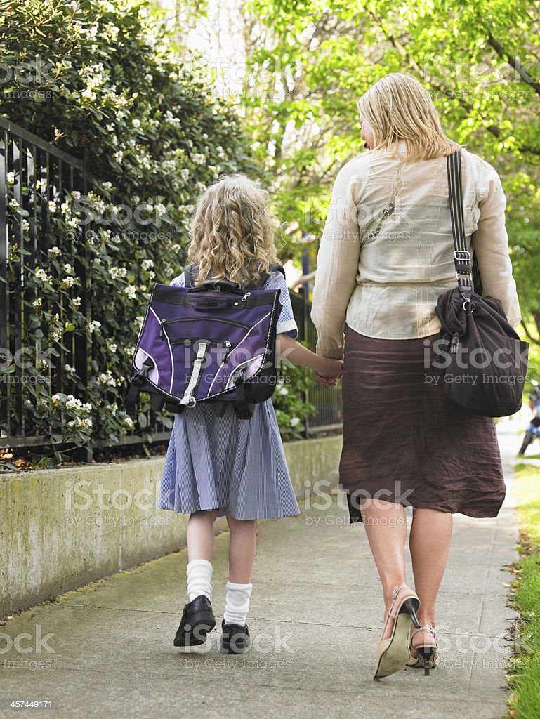 Girl Walking With Mother On Pavement stock photo