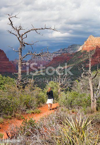 A teenage girl walks along a red dirt path at Yavapai scenic overlook with striking red rock formations in the distance on a warm cloudy afternoon, Sedona, Arizona, USA