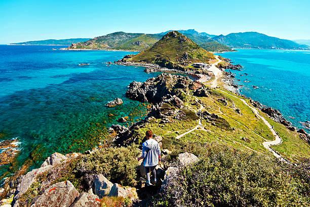 fille marchant le long de la péninsule de parata génois tour - randonnée corse photos et images de collection