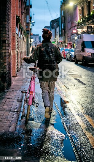 Manchester, UK - April 14, 2019: Girl walks home with her bicycle after rain in Manchester, UK