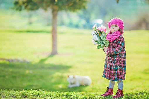 A girl walks in the park. A child in a warm coat walks on a green lawn in the woods in early spring