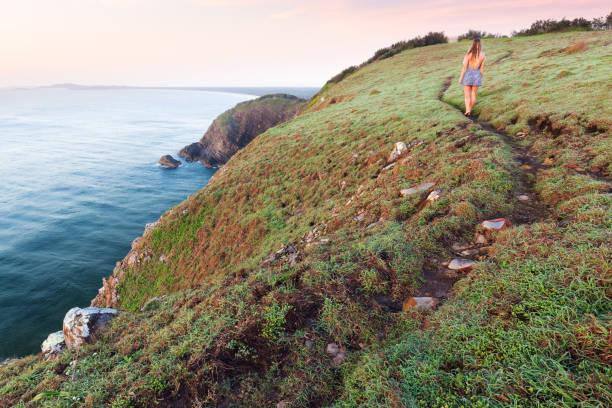 Girl Walks on Coastal Trail stock photo