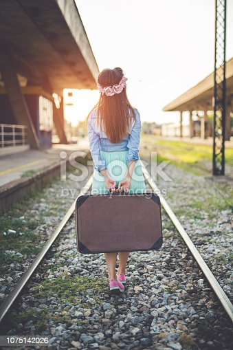 Young beautiful girl walks the train tracks with a suitcase