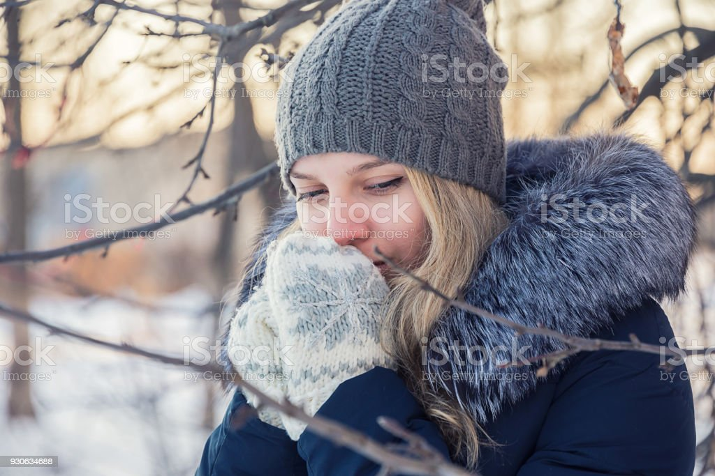 girl warms her hands in mittens stock photo