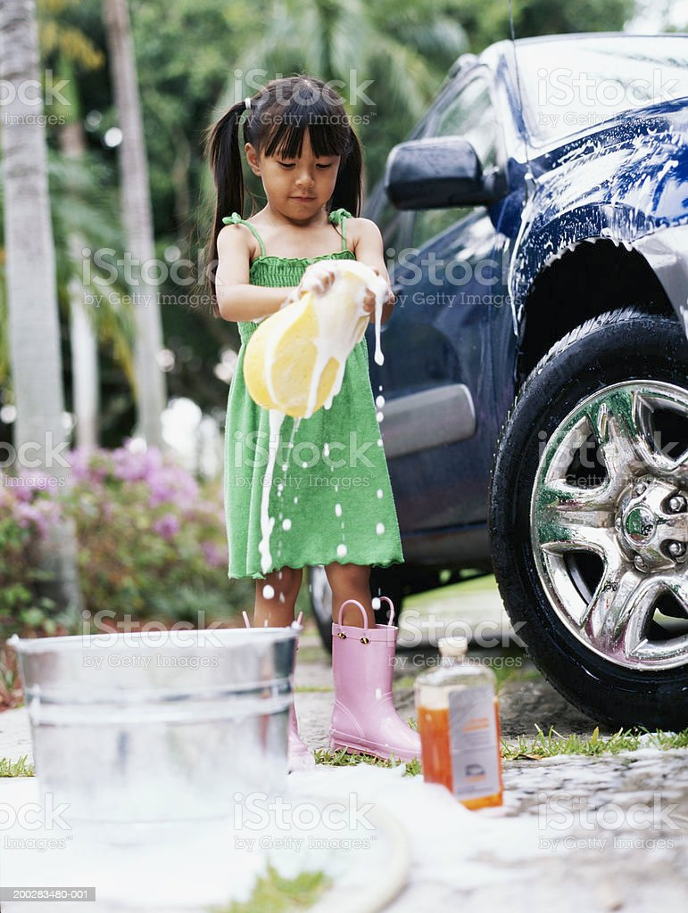 Girl (4-6) washing car in driveway, squeezing sponge, low angle view stock photo