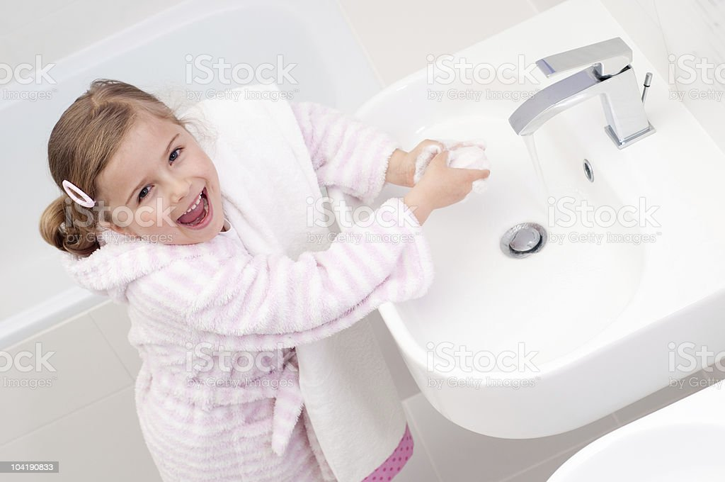 girl washing hands in bathroom stock photo