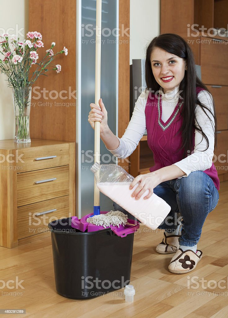 girl washing parquet floor with detergent stock photo
