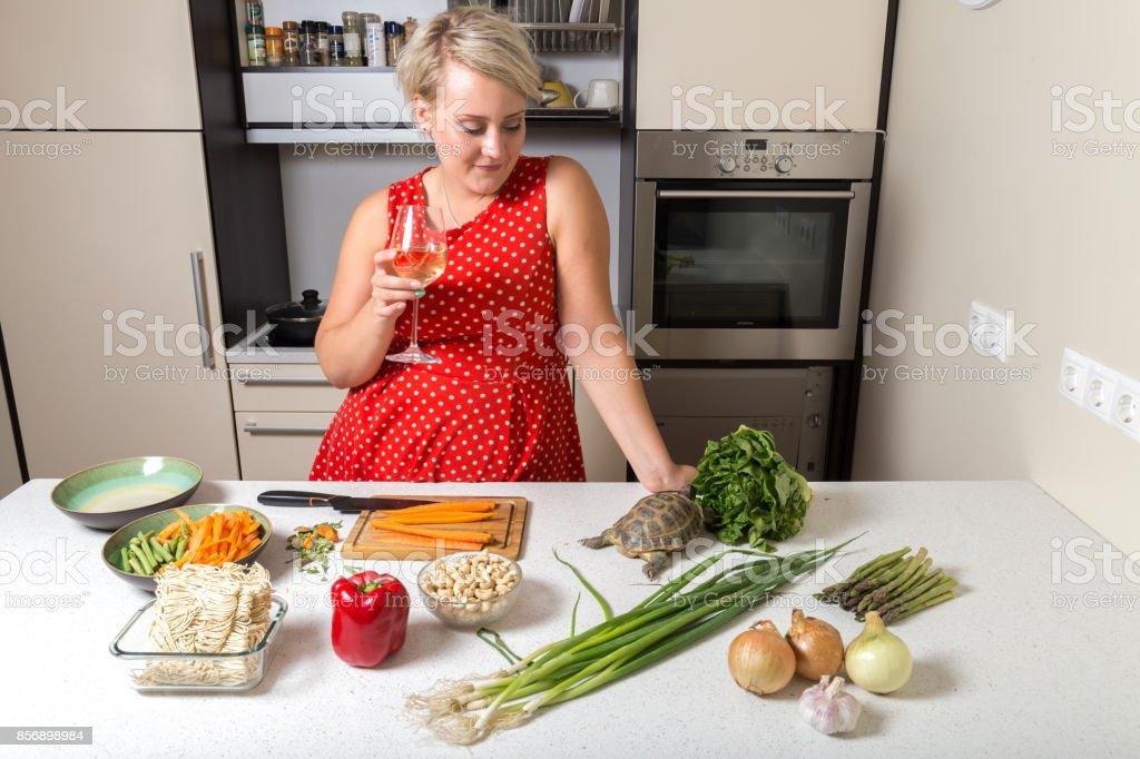 Girl watches tortoise eating on salad stock photo