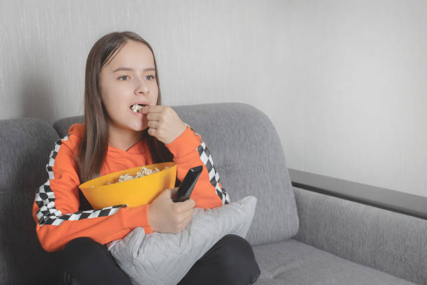 Girl watching a movie, sitting with the remote control on the couch, eating popcorn stock photo