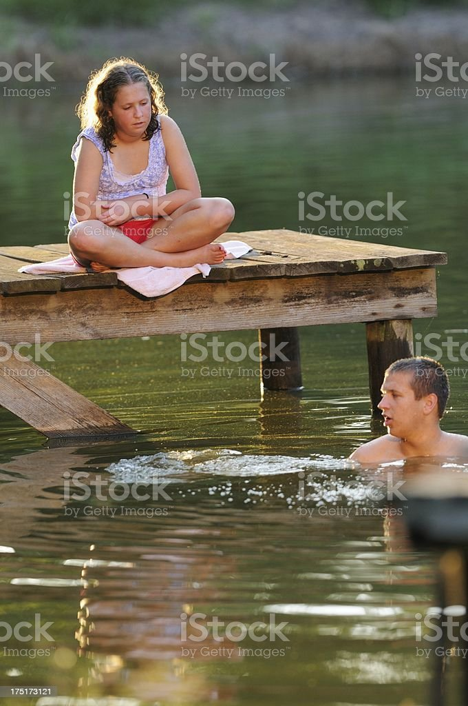 Girl watching boy swimming in pond royalty-free stock photo