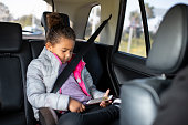 Girl watching cartoons on mobile phone during the trip.
