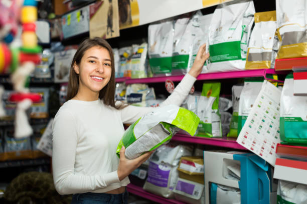 Femme regardant la nourriture au sec en magasin pour animaux de compagnie - Photo