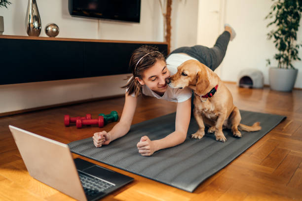 girl watching exercise tutorials online with her dog stock photo