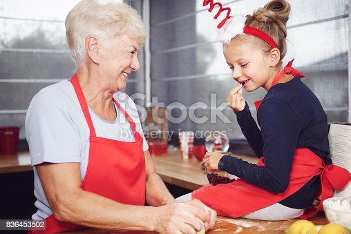 istock Girl watching her grandmother make dough 836453502