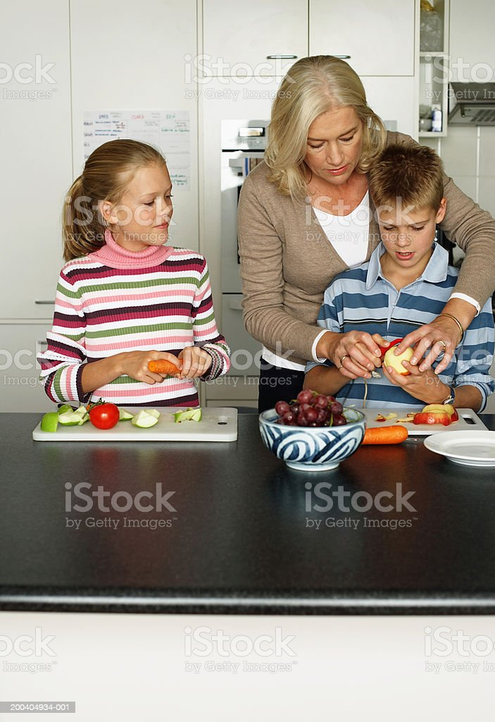 Girl (10-12) watching mother assist twin brother peel apple royalty-free stock photo